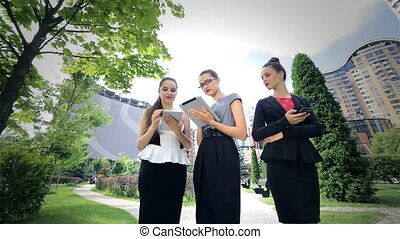 Three successful business woman working on the tablet, discuss news and delight