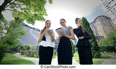 Three successful business woman working on the tablet take calls