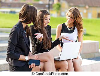 Three Successful businesswomen in the city on a bench discussed