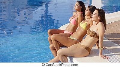 Three sun loving young women in bikinis