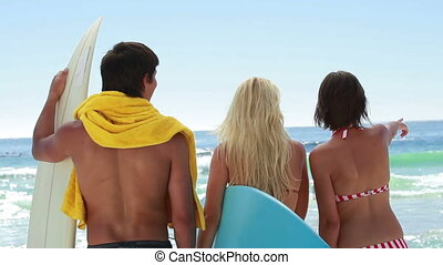 Three surfers looking out at the water