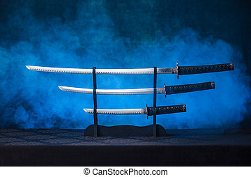 Three swords on a stand with exposed blades - Katana, ...