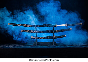 Three swords on stand, one blade partially visible - Katana...