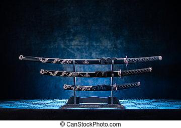 Three swords on stand, with dramatic blue light - Katana, ...