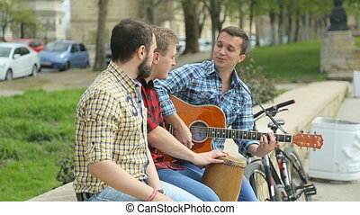 Three talented guy perform on the street with passion -...