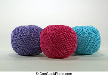 three tangle of purple, burgundy and blue natural cotton for needlework on white background