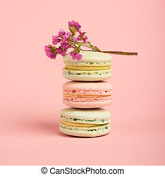 Three tasty colorful macarons on the pink background.