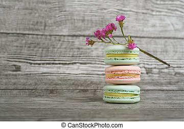 Three tasty colorful macarons on the wooden background.