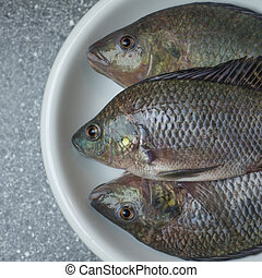 three tasty tilapia freshly cought - Serving fish at local...