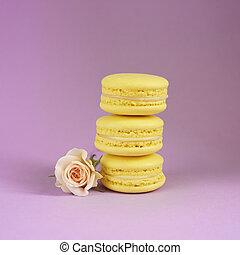 Three tasty yellow macarons on the purple background.