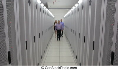 Three technicians walking in hallway and smiling