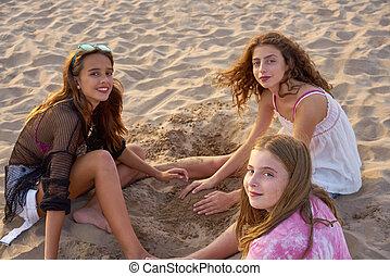 Three teen girls playing with the beach sand - Three teen...