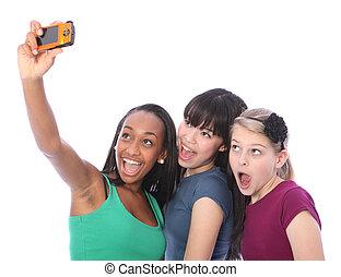 Three teenage girl friends fun with digital camera