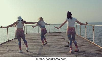Three teenage girls dancing dance hall on the docks near sea