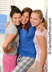 Three teenage girls laughing in pajamas