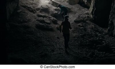Three teenagers climbing from the dark cave, clsoe up