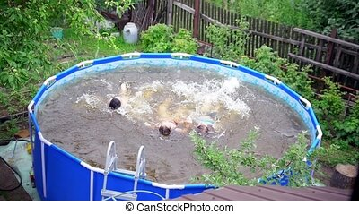 Three teenagers dive in swimming pool outdoors at summer...