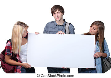 Three teenagers holding message board