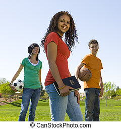 Three teens with bible hang out at a park