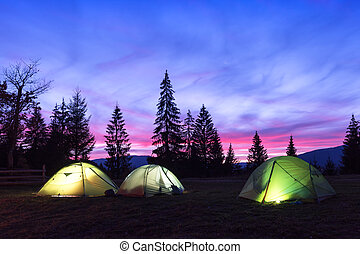 Three tents lighted from the inside