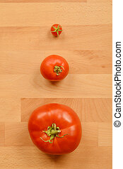Three tomatos on a wooden cutting board