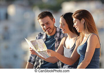 Three tourists checking map in a town