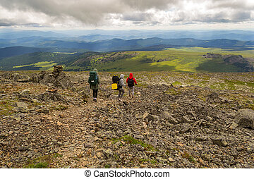 Three tourists two girls and one boy with backpacks go down the hill on the rocks towards the green fields, adventures under the blue sky and clouds in altai mountains named sarlyk