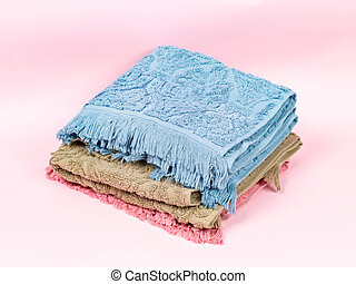 Three towels of different colors stacked in a stack on a pink background
