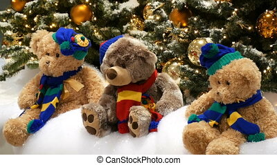 Three toy bears sit under Christmas trees, beautifully...