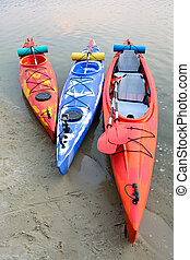 Three Traveling Kayaks on the Sand Beach near Beautiful River or Lake at the Evening. Travel and Adventure Concept.