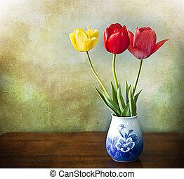 three tulips in china vase on grunge background