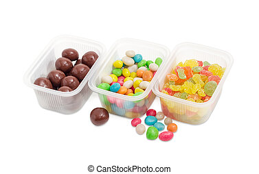 Three variety of different candies in small plastic containers