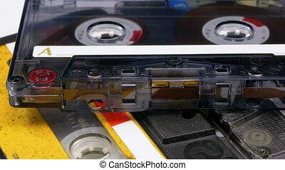 Three Vintage Audio Cassettes Rotate on White Background....