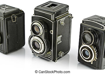 Three Vintage two lens photo cameras isolated on white