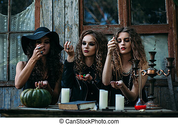 Three vintage witches perform magic ritual, throwing sweet ...