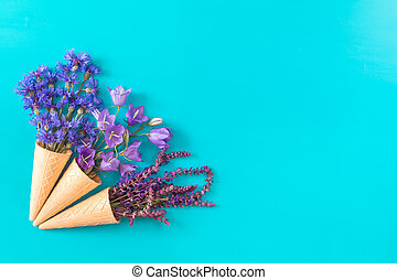 Three waffle cones with flowers blossom bouquets on blue surface.