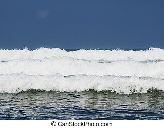 Three ocean waves breaking with clean blue sky in the background