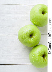 Three wet green apples on white wooden background. Copy space. Top view.