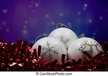 Three white Christmas balls with snowflake and reindeer in front of purple blue background.