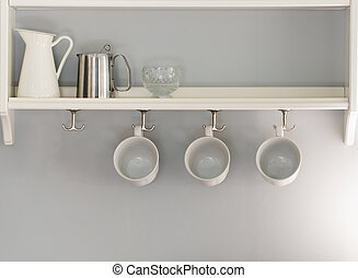 three white coffee cups hanging in a row. jug and glass sitting on shelf