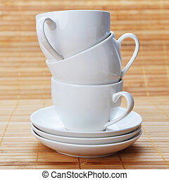 three white coffee cups with saucers on wooden background white