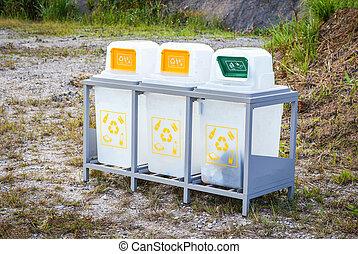 Three white recycling bin in the garden park