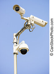 Three white urban CCTV security cameras