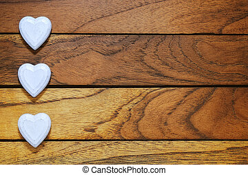 three whites hearts lined with wood background