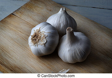 Three Whole Garlic Bulbs on Wooden Chopping Board