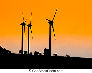 Three wind turbines used for ecological producing electric energy. Sunset silhouettes