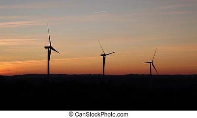 three windmills at orange sunset