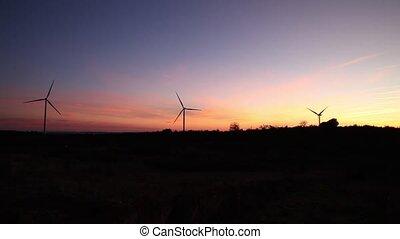 three windmills at panoramic sunset