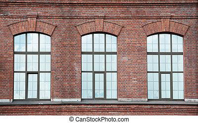 Three window on a red bric wall