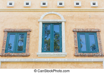 Three windows and a brick wall